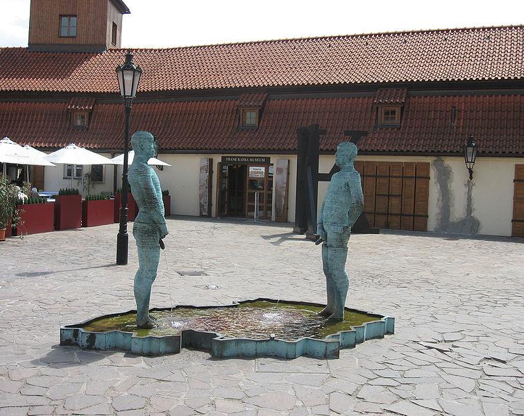 """""""Sikający"""" rzeźba Davida Černego z 2004, zlokalizowana w Pradze przy ul. Cihelní 2b, obok Muzeum Franza Kafki. Rzeźba przedstawia dwóch mężczyzn (po 210 cm wysokości), stojących naprzeciw siebie i oddających mocz do basenu w kształcie Czech. Penisy mężczyzn są ruchome, a strumień wody może być kierowany przez osoby oglądające za pomocą SMS-ów. fot Wikipedia"""